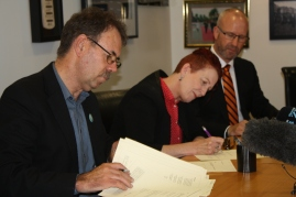 Cee signs the terms of settlement for the caregiver's offer in parliament on behalf of NZNO after two years of negotiations. John Ryall negotiator from E tū picture at left.